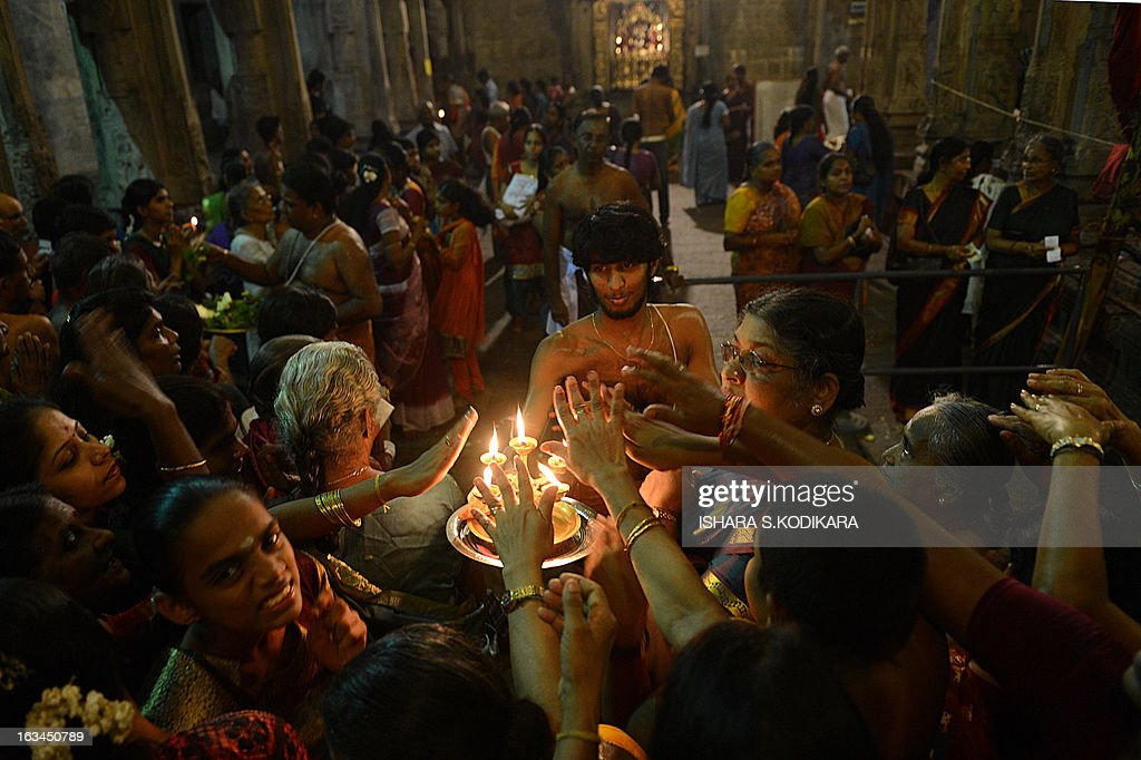 Sri Lankan Hindus receive blessings from a priest holding an oil lamp during the Maha Shivaratri festival at a temple in Colombo on March 10, 2013. The festival of Maha Shivaratri is marked by Hindus fasting and offering prayers in a night long vigil. AFP PHOTO/ Ishara S. KODIKARA