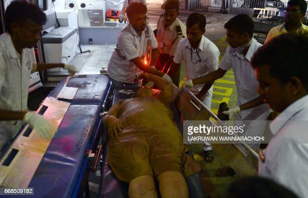 Sri Lankan hospital workers bring in a wounded woman to the main hospital in Colombo on April 14 following a massive rubbish dump fire Emergency...