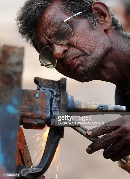 A Sri Lankan ironworker welds material at a building site in Colombo on May 23 2014 Sri Lanka's economy recorded 80 percentplus growth for two...