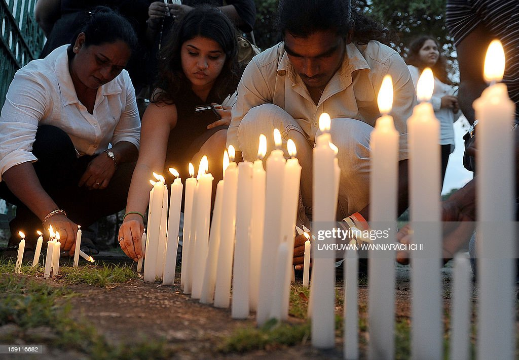 Sri Lankan journalists and well wishers light candles in front of a photograph of slain editor Lasantha Wickrematunge in the capital Colombo on January 8, 2013, on his fourth death anniversary. International media rights groups criticised Sri Lanka for failing to identify the assassins of Wickrematunge, a top anti-establishment editor. AFP PHOTO/ LAKRUWAN WANNIARACHCHI