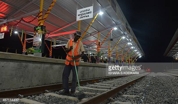 A Sri Lankan labourer cleans the tracks at the Jaffna railway station the capital of Sri Lankas northern province October 12 a day ahead of its...