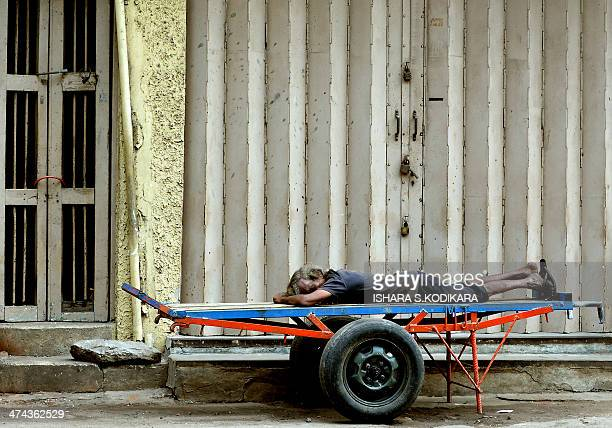 A Sri Lankan labourer sleeps on a cart at the main market in Colombo on February 23 2014 Sri Lanka's economy recorded 80 percentplus growth for two...