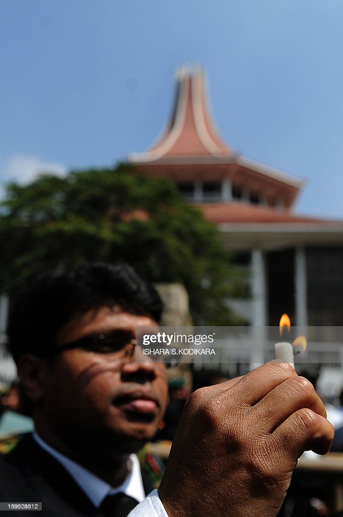 A Sri Lankan lawyer holds a lit candle during a protest against the government's move to impeach Chief Justice Shirani Bandaranayake, in front of the Supreme Court in Colombo on January 15, 2013. Sri Lanka President Mahinda Rajapakse on Tuesday appointed the government's senior legal advisor Mohan Peiris as a replacement for the impeached chief brushing off protests from lawyers and rights group. Peiris was sworn-in before the president shortly after parliament approved his appointment with immediate effect, an official of the president's press office said. AFP PHOTO/ Ishara S