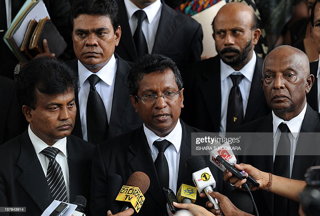 Sri Lankan lawyer J. C. Weliamuna (C) speaks with reporters outside the Sri Lankan Supreme Court in Colombo on December 6, 2012. Sri Lanka's top judge Shirani Bandaranayake stormed out of her impeachment hearing after government lawmakers called her a 'mad woman' and displayed open hostility during an unfair trial, her lawyers said. The move to impeach the country's first female chief justice, came after she scuttled several bills, including one that gave more powers to President Mahinda Rajapakse's youngest brother Basil, the economic development minister. AFP PHOTO/ Ishara S.KODIKARA