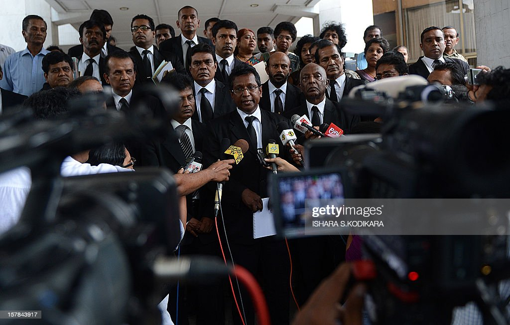 Sri Lankan lawyer J. C. Weliamuna (C) speaks with reporters outside the Sri Lankan Supreme Court in Colombo on December 6, 2012. Sri Lanka's top judge Shirani Bandaranayake stormed out of her impeachment hearing after government lawmakers called her a 'mad woman' and displayed open hostility during an unfair trial, her lawyers said. The move to impeach the country's first female chief justice, came after she scuttled several bills, including one that gave more powers to President Mahinda Rajapakse's youngest brother Basil, the economic development minister. AFP PHOTO/ Ishara S
