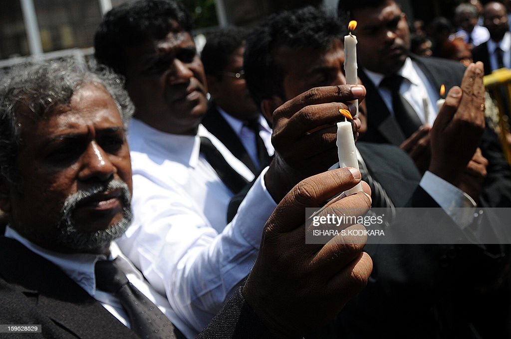 Sri Lankan lawyers hold lit candles during a protest against the government's move to impeach Chief Justice Shirani Bandaranayake, in front of the Supreme Court in Colombo on January 15, 2013. Sri Lanka President Mahinda Rajapakse on Tuesday appointed the government's senior legal advisor Mohan Peiris as a replacement for the impeached chief brushing off protests from lawyers and rights group. Peiris was sworn-in before the president shortly after parliament approved his appointment with immediate effect, an official of the president's press office said. AFP PHOTO/ Ishara S