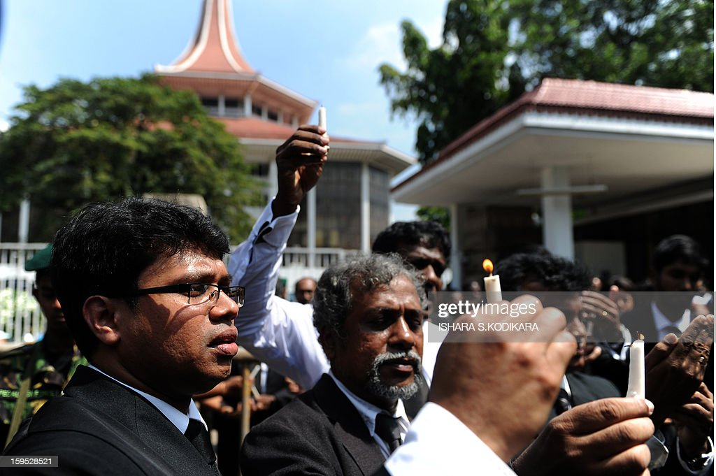 Sri Lankan lawyers holds a lit candles during a protest against the government's move to impeach Chief Justice Shirani Bandaranayake, in front of the Supreme Court in Colombo on January 15, 2013. Sri Lanka President Mahinda Rajapakse on Tuesday appointed the government's senior legal advisor Mohan Peiris as a replacement for the impeached chief brushing off protests from lawyers and rights group. Peiris was sworn-in before the president shortly after parliament approved his appointment with immediate effect, an official of the president's press office said. AFP PHOTO/ Ishara S.KODIKARA