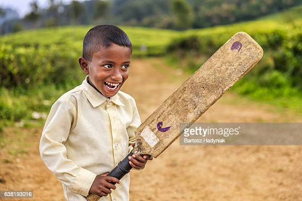 Sri Lankan little boy playing cricket on tea plantation