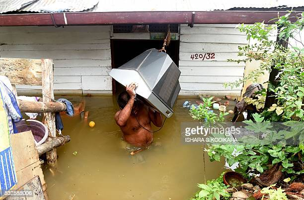A Sri Lankan man carries a television through floodwaters from a home in the Kelaniya suburb of Colombo on May 19 2016 Sri Lankan troops recovered...