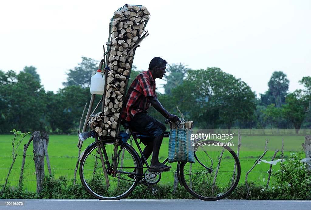 A Sri Lankan man cycles his bicycle laden with firewood to be sold in the northern town of Kilinochchi on November 17 2013 Commonwealth leaders...