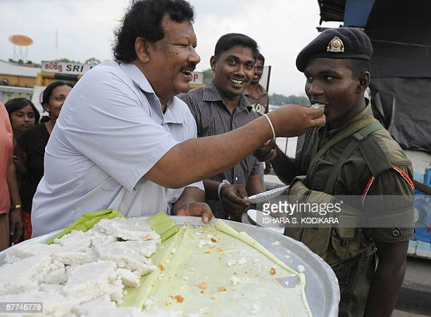 A Sri Lankan man feeds a soldier with the milk rice pudding to celebrate the country's military victory against the LTTE rebels in Colombo on May 18...