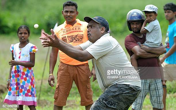 A Sri Lankan man participates in a traditional 'Catch the Egg Toss' game in a field during Sinhala and Tamil New Year celebrations in Kirindiwela on...
