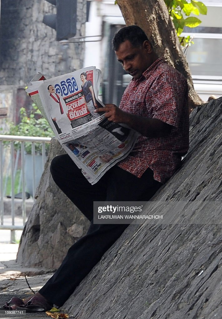 A Sri Lankan man reads a local newspaper carrying headlines on the sacking of Chief Justice Shirani Bandaranayake, in Colombo on January 13, 2013. Sri Lankan President Mahinda Rajapakse sacked the chief justice by ratifying a controversial parliamentary vote, defying international calls for restraint and plunging the country into a constitutional crisis.