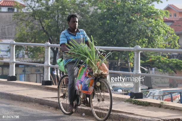 Sri Lankan man rides his bicycles as he carry vegetables in Colombo the capital of Sri Lanka on July 10 2017 An island country Sri Lanka is famous...