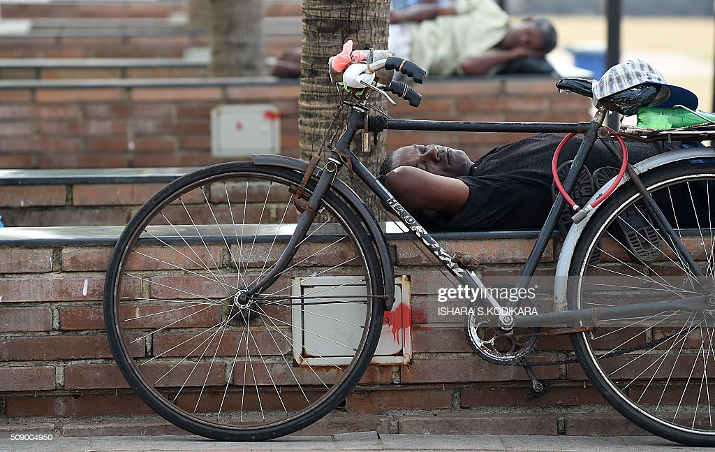 A Sri Lankan man sleeps on a street in Colombo on February 8, 2016. AFP PHOTO/ Ishara S. KODIKARA / AFP / Ishara S.KODIKARA