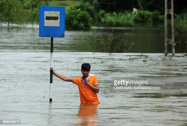 Sri Lankan man stands in floodwaters in Bulathsinhala in Kalutara district on May 27 2017 Rainfall on May 26 triggered the worst flooding and...