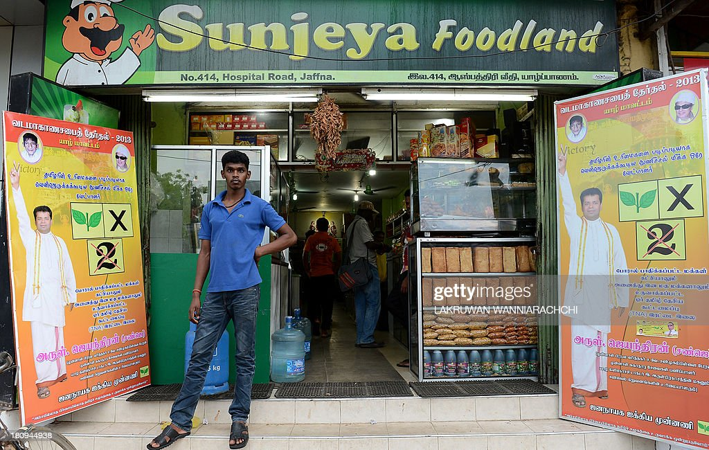 A Sri Lankan man stands outside a supermarket with election posters in Jaffna, 400 kilometres (250 miles) north of the capital Colombo on September 18, 2013. Sri Lanka is holding the first ever provincial council election, scheduled for September 21. AFP PHOTO/LAKRUWAN WANNIARACHCHI