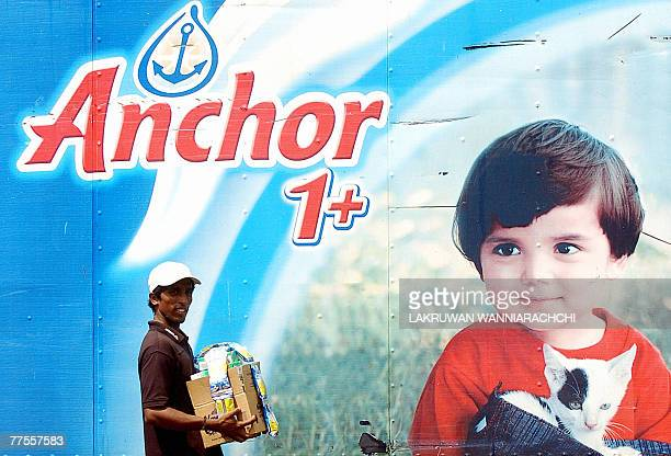 A Sri Lankan man walks past a billboard advertising milk powder in the streets of Colombo 30 October 2007 amidst a shortage of milk in the market...