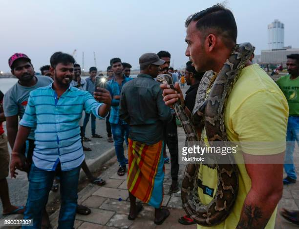 A Sri Lankan man wraps a fullgrown pet python reptile on his neck as one of his friends takes a photograph at one of the more popular recreation...