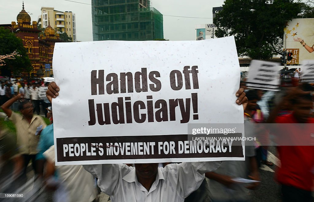 A Sri Lankan Marxist JVP party activist holds up a placard during a protest against government moves to sack the country's first woman chief justice amid allegations that her impeachment was a blow to democracy, in the capital Colombo on January 7, 2013. Sri Lanka's Court of Appeal Monday ordered parliament to drop its controversial impeachment of the country's top judge amid international concern for judicial independence on the island.
