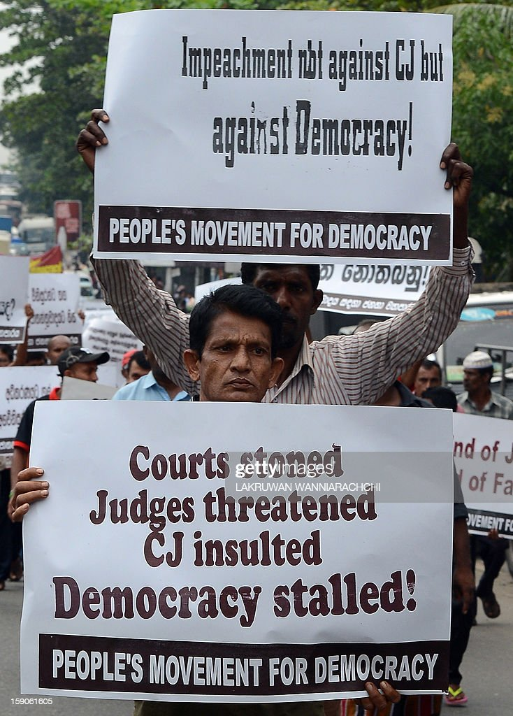 Sri Lankan Marxist JVP party activists hold placards during a protest against government moves to sack the country's first woman chief justice amid allegations that her impeachment was a blow to democracy, in the capital Colombo on January 7, 2013. Sri Lanka's Court of Appeal Monday ordered parliament to drop its controversial impeachment of the country's top judge amid international concern for judicial independence on the island. AFP PHOTO/ LAKRUWAN WANNIARACHCHI