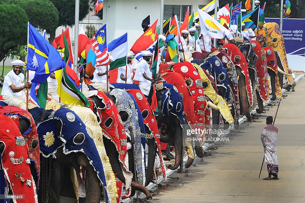 Sri Lankan men in traditional costume hold national flags of the Commonwealth countries as they sit atop elephants outside the Bandaranaike Memorial...
