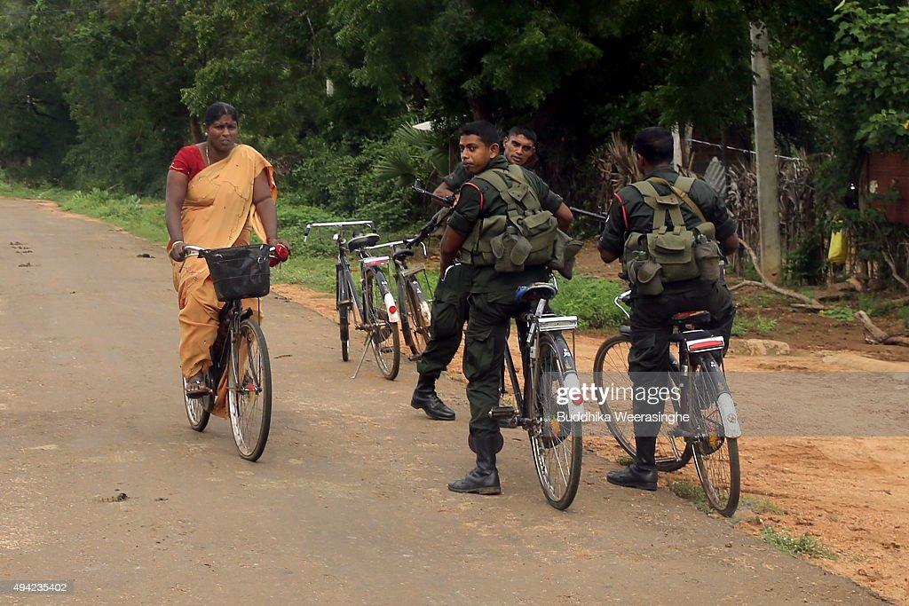 Sri Lankan military person patrol in street as an ethnic Tamil woman ride bicycle on October 25 2015 in Kilinochchi Sri Lanka Sri Lankan Prime...