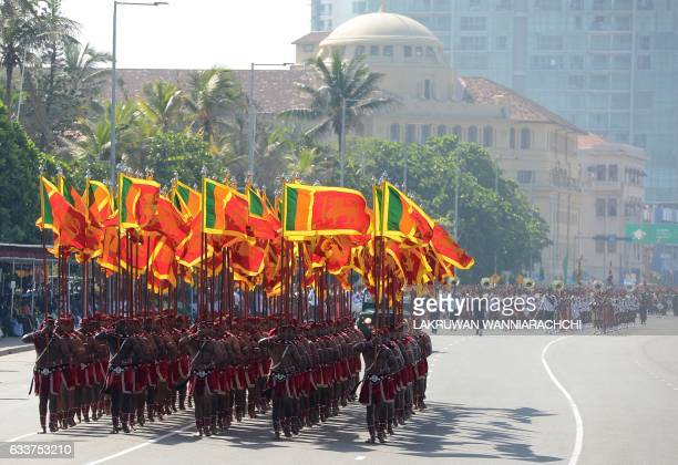 Sri Lankan military personnel march with the national flag during the island's 69th Independence Day celebrations in Colombo on February 4 2017 Sri...