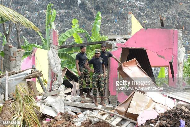 Sri Lankan military personnel stand among damaged homes at the site of a collapsed garbage dump in Colombo on April 15 2017 The death toll from a...