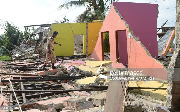 A Sri Lankan military personnel walks through damaged homes at the site of a collapsed garbage dump in Colombo on April 15 2017 The death toll from a...