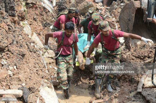 Sri Lankan military rescue workers recover the body of a man during a rescue operation at the site of a collapsed garbage dump in Colombo on April 15...