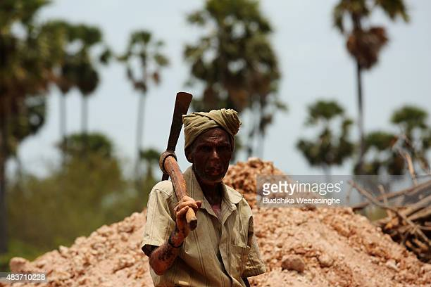 Sri Lankan minority ethnic Tamil man holds pick axe as he stands in the land which has been recently released back to owners in April after 25 years...