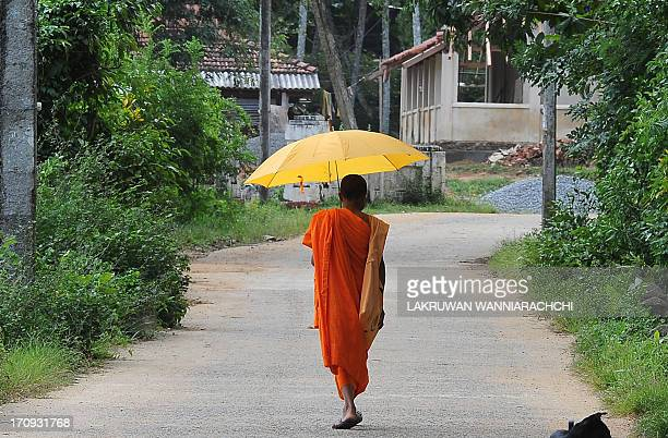 A Sri Lankan monk walks down a road in the southern district of Matara on June 20 2013 Sri Lanka a Buddhist majority country will celebrate on June...