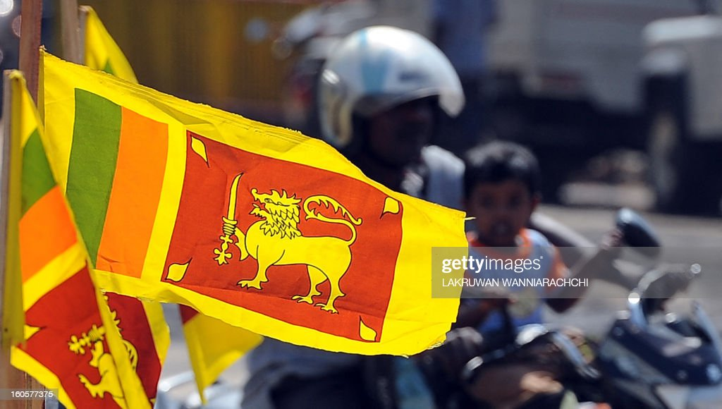 A Sri Lankan motorcyclist drives past Sri Lankan national flags in the north-eastern town of Trincomalee on February 3, 2013 ahead of Independence Day. Sri Lanka will celebrate its 65th national day on February 4 .