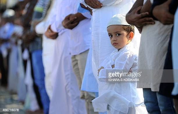 A Sri Lankan Muslim child looks on as prayers are said during Eid AlAdha celebrations at the Galle Face esplanade in Colombo on October 6 2014...