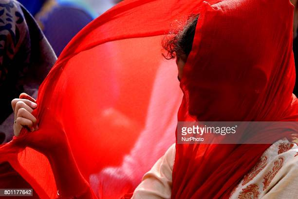 A Sri Lankan muslim girl adjusts her veil that blows in the wind as she prays during Eid alFitr prayers to mark the end of the holy fasting month of...