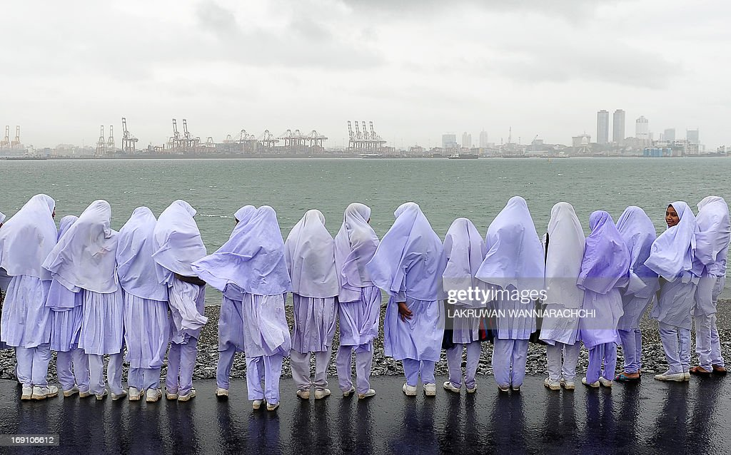 Sri Lankan Muslim school girls stand on the edge of a sea port in Colombo on May 20, 2013, after travelling from their town of Kalmunai, over 370 kilometres (231 miles) east of the capital Colombo. Work on a USD 500-million new container terminal is nearing completion at Colombo which is a key transhipment hub for Indian cargo. AFP PHOTO/ LAKRUWAN WANNIARACHCHI