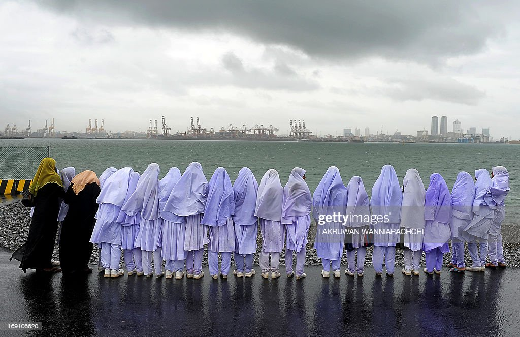 Sri Lankan Muslim school girls stand on the edge of a sea port in Colombo on May 20, 2013, after travelling from their town of Kalmunai, over 370 kilometres (231 miles) east of the capital Colombo. Work on a USD 500-million new container terminal is nearing completion at Colombo which is a key transhipment hub for Indian cargo.