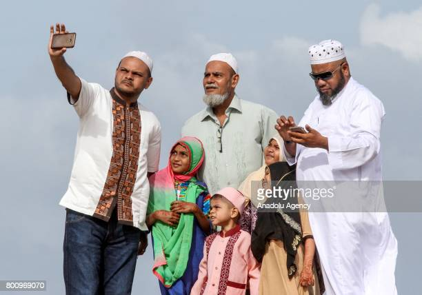 Sri Lankan Muslims gather prior to attend Eid alFitr prayer during the Eid alFitr holiday at the Galle Face green in Colombo Sri Lanka on July 26...