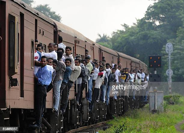 Sri Lankan office workers walk past a crowded passenger train headed to Colombo on Thursday July 10 2008 Train is a popular mode of transport in this...