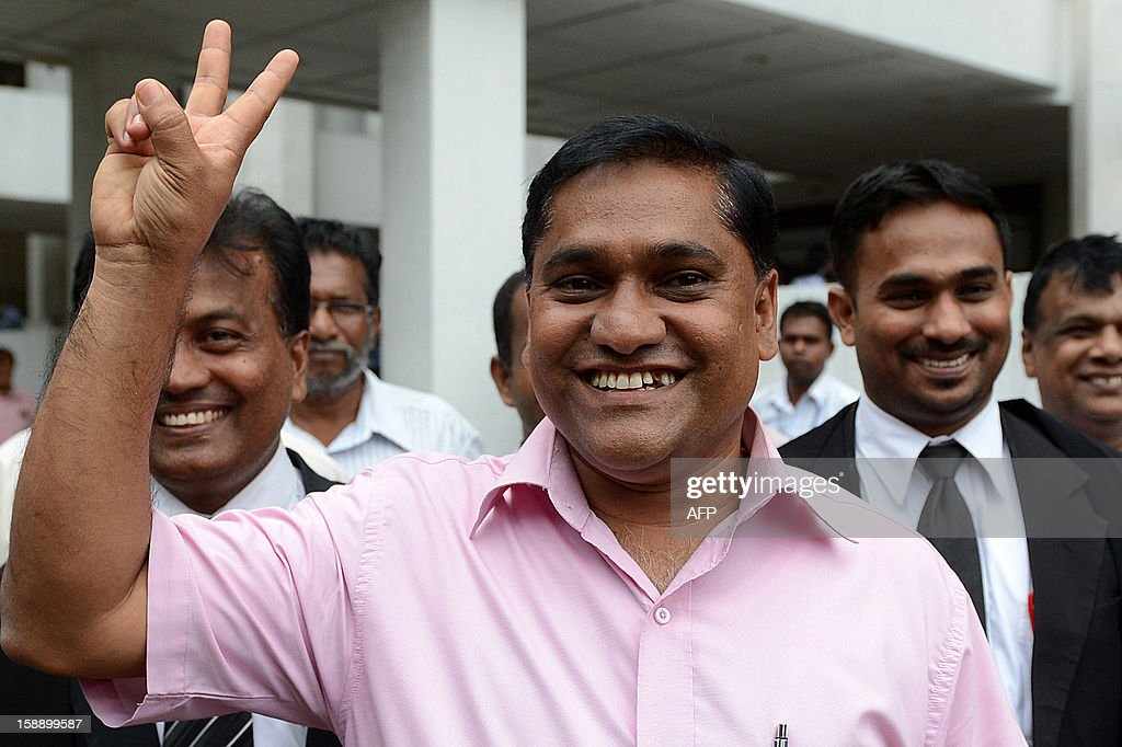Sri Lankan opposition lawmaker Vijitha Herath makes a victory sign outside the Superior Courts Complex in Colombo on January 3, 2013, after a Supreme Court decision that virtually struck down a move by the ruling party to impeach the Chief Justice Shirani Bandaranayake. The Court held that parliament could not use its own standing orders to try the chief justice who faces allegations of misconduct from the ruling party after she struck down several bills of the government. AFP PHOTO/ Ishara S