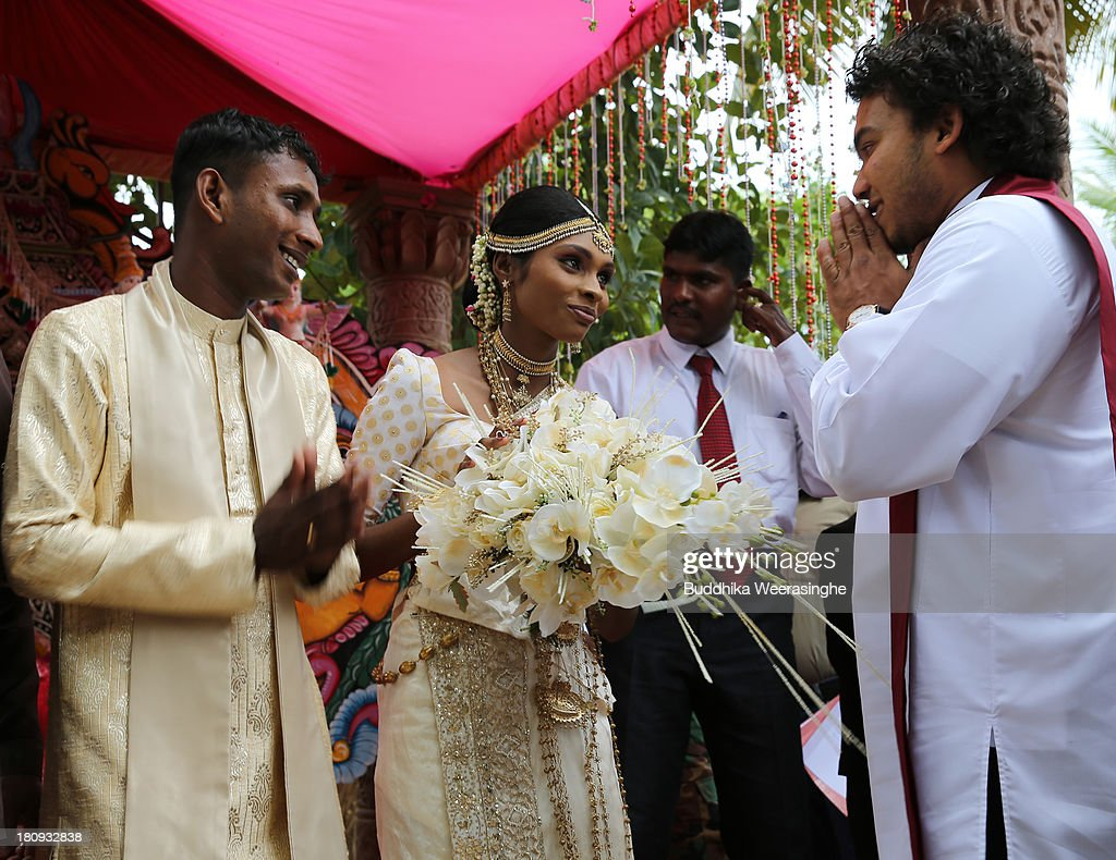 Sri Lankan Parliamentarian and the President son Namal Rajapaksa (R) congratulates a former female Tamil rebel named Premarathnam Suganthini(C), 19 years old, and her groom H.N. Rathnayaka, 23 years old, during the weeding ceremony at the Civil Defence Force militray camp on September 18, 2013 in Vishwamadu, Sri Lanka. The former female Tamil rebel and a Sinhalese military officer were legally married today in Sri Lanka's war-torn Northern province. Sri Lanka suffered through a 26-year civil war between the Tamil Tigers and the Sri Lankan military which ended in 2009. On September 21 Sri Lankans of the Northern Province will head to the polls for provincial council elections for the first time since the conflict began.