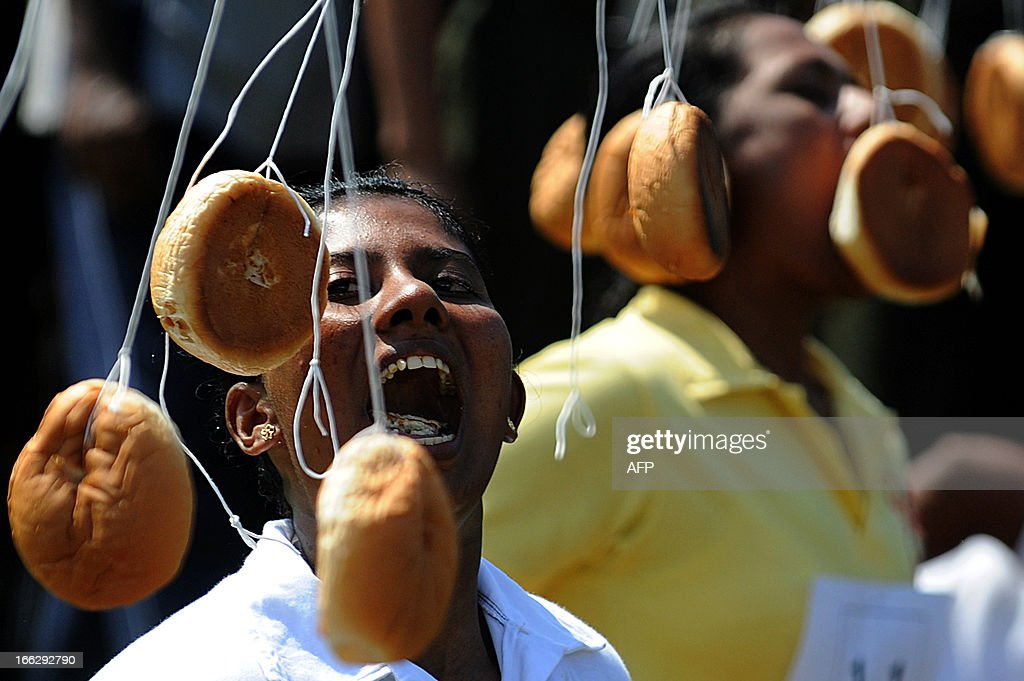 A Sri Lankan participant tries to bite a bun tied on a string during traditional Sinhala and Tamil New Year celebrations in Colombo on April 11, 2013. The New Year dawns on April 14 and traditional fun and games are organised across the island to celebrate the occasion. AFP PHOTO/Ishara S. KODIKARA