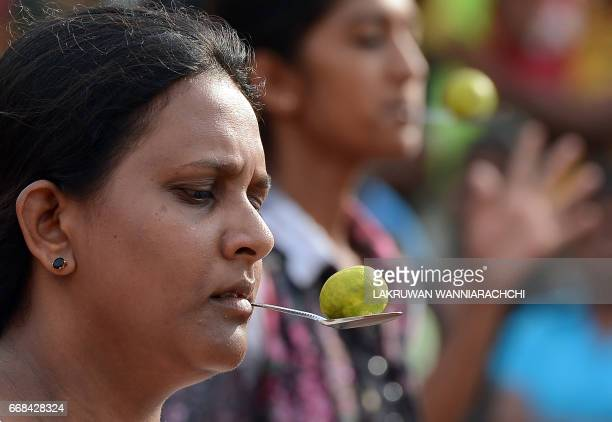Sri Lankan participants use a lemon and spoon at Piliyandala near Colombo on April 14 as they take part in traditional festival games held to...