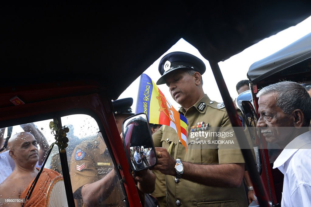 Sri Lankan Police Chief N.K. Illangakoon(C) ties a Buddhist flag on a three-wheeler taxi in Colombo on May 23, 2013, ahead of the country's main Buddhist festival of Wesak. Sri Lankan Buddhists are preparing to celebrate Wesak, which commemorates the birth of Buddha, his attaining enlightenment and his passing away on the full moon day of May which falls on May 24 this year. AFP PHOTO/Ishara S. KODIKARA