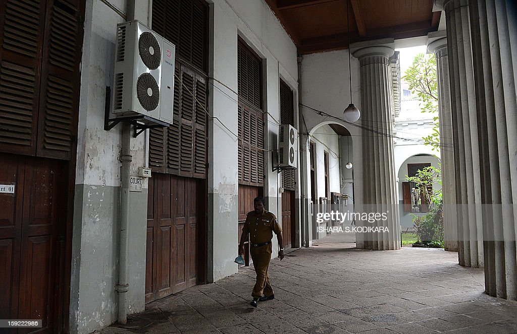 A Sri Lankan police officer walks at the deserted High Court as Sri Lankan lawyers stage a work stay away in the capital Colombo on January 10, 2013. Sri Lanka's lawyers staged a strike Thursday to protest the impeachment of the country's top judge which has raised concern about judicial independence on the previously war-ravaged Indian Ocean island. Work in court houses came to a stand still as some 11,000 lawyers of the influential Bar Association stayed away and protested in the centre of the capital Colombo after being prevented from marching to parliament. AFP POHOTO/ Ishara S