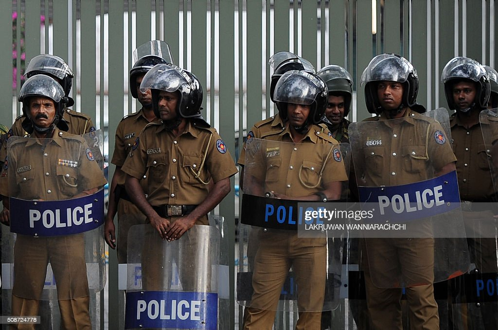 Sri Lankan police officials stand guard as members of a Sri Lankan fringe opposition group take part in a demonstration outside the United Nations offices in Colombo on February 6, 2016. The United Nations' human rights chief Zeid Ra'ad Al Hussein began his first visit to Sri Lanka on February 6 to gauge the island's progress in investigating allegations troops committed atrocities during a prolonged civil war. AFP PHOTO / LAKRUWAN WANNIARACHCHI / AFP / LAKRUWAN WANNIARACHCHI