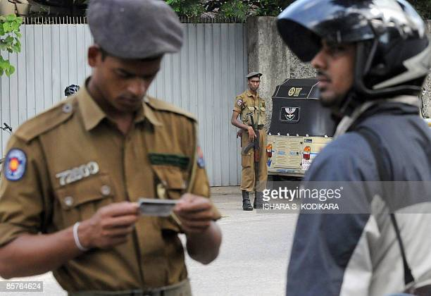 A Sri Lankan policeman stands guard as a comrade checks the identity document of a motorcyclist in Colombo on April 2 2009 Sri Lankan government...