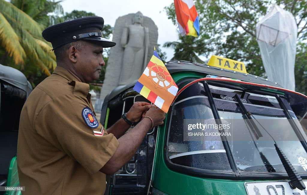 A Sri Lankan policeman ties a Buddhist flag on a three-wheeler taxi in Colombo on May 23, 2013, ahead of the country's main Buddhist festival of Wesak. Sri Lankan Buddhists are preparing to celebrate Wesak, which commemorates the birth of Buddha, his attaining enlightenment and his passing away on the full moon day of May which falls on May 24 this year. AFP PHOTO/Ishara S. KODIKARA