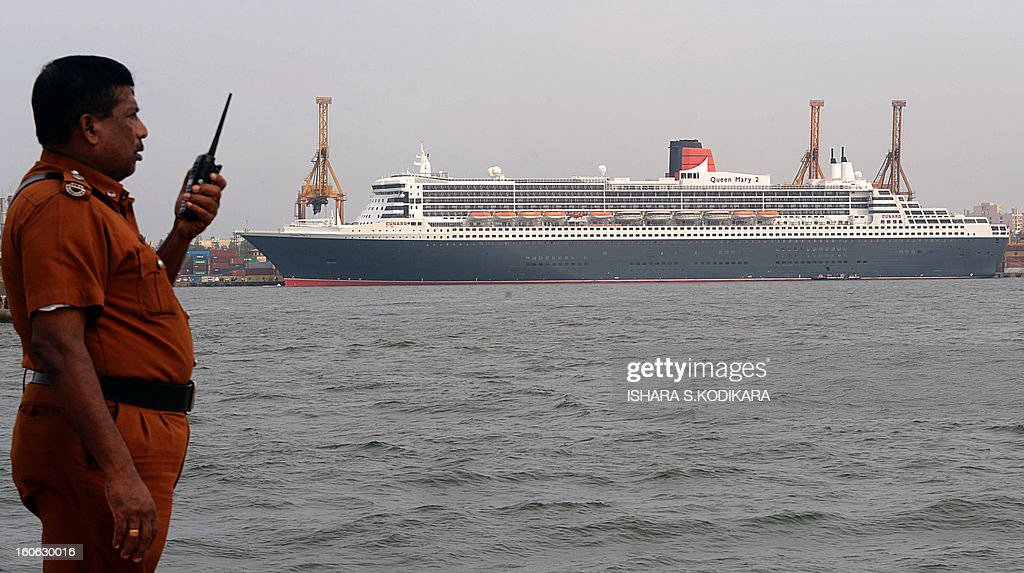 A Sri Lankan Port Authority security guard keeps watch as the RMS Queen Mary 2 is pictured during a brief stopover at the Colombo harbour on February 4, 2013. The luxury cruise liner brought over 2,300 tourists to Sri Lanka which is emerging from nearly four decades of ethnic war and has become an upmarket holiday destination. AFP PHOTO/ Ishara S